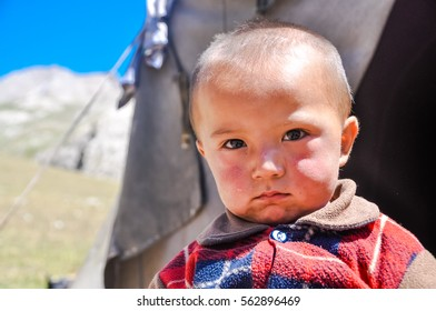 Arslanbob, Kyrgyzstan - circa July 2011: Small native child with teardrop on his sad face poses in Arslanbob, Kyrgyzstan. Documentary editorial.