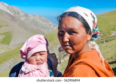 Arslanbob, Kyrgyzstan - circa July 2011: Native woman with headcloth poses with her small daughter in Arslanbob, Kyrgyzstan. Documentary editorial.