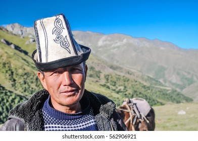 Arslanbob, Kyrgyzstan - circa July 2011: Native man with traditional hat with ornaments poses in mountainous countryside of Arslanbob, Kyrgyzstan. Documentary editorial.
