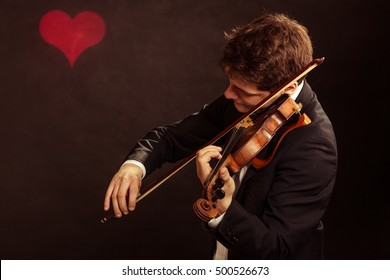 Art and artist. Young elegant in love man violinist fiddler playing violin on black background with valentine heart love symbol. Classical music. Studio shot.