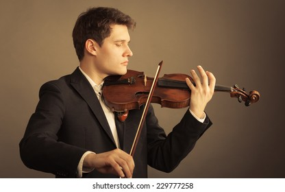 Art and artist. Young elegant man violinist fiddler playing violin on brown. Classical music.