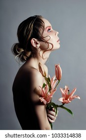 Art beauty girl face closeup with lilies in hands on grey background. Cosmetics and makeup, body and face skin care, contrast makeup, big beautiful eyes women