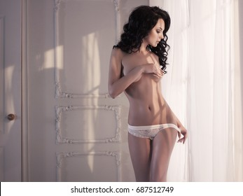 Art boudoir fashion photo of beautiful gorgeous woman in lingerie at the window. Perfect body. Beauty and health. Wedding style. Bridal morning