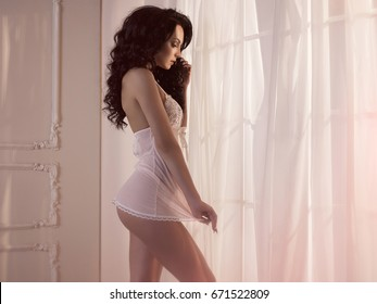 Art boudoir fashion photo of nude elegant woman at the window. Perfect body. Beauty and health