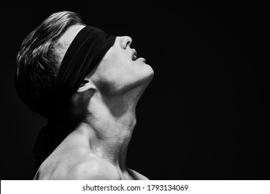 Art close up portrait of a handsome athletic young blindfold man body. Men's beauty and health. Copy space.