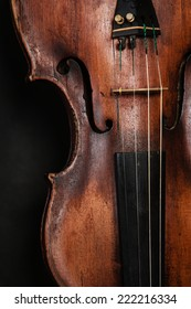 Art. Closeup of old wooden violin stringed instrument on dark gray. Classical music.