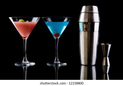 Art of cocktails. Betty Blue cocktail, Cosmopolitan cocktail, Shaker and Measure glass over black background.