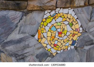Art of colored ceramic scraps in flagstone wall