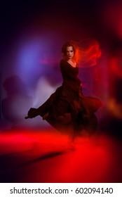 Art concept. Beautiful young woman dancer performing tango at studio.