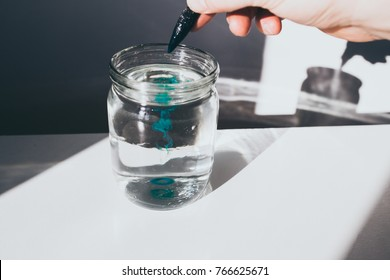 Art concept photo-watercolor paint,blue paint splatter,aquarelle,glass of water,palete,hand with brush,scene with shadows.