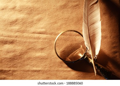 Art concept. Vintage magnifying glass near feather on nice old paper background