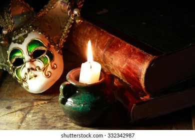 Art concept. Vintage still life with old books near Venetian mask and lighting candle