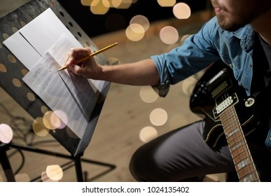 art and creativity concept - man with guitar writing notes to music book at studio over festive lights