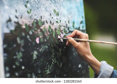 Art, creativity and people concept - close up of artist with palette and brush painting still life on paper at studio outdoor. Picture of field flowers