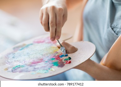 art, creativity and people concept - close up of artist with palette knife painting still life on easel at studio