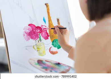 art, creativity and people concept - close up of artist with paint brush and easel painting still life on paper at studio