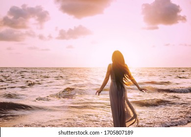 Art dark mysterious silhouette woman on sea shore nature air. Meditation prayer spiritual blessing divine calm. Summer Sun light. Happy Young princess long dress hair fluttering. back View. joy travel