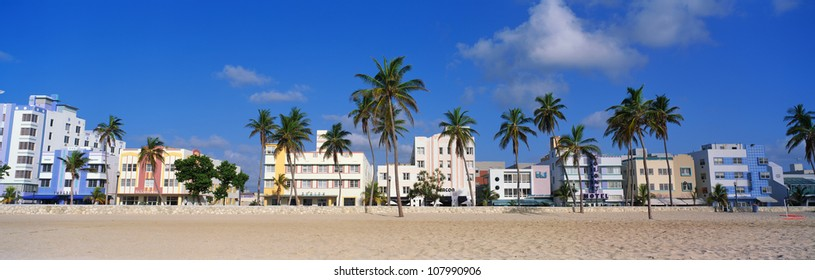 Art deco district of South Beach Miami. The buildings are painted in pastel colors surrounded by tropical palm trees.