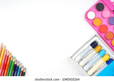 Art and design concept. Art supplies suc as watercolor, brushes creatively arranged on a white desk