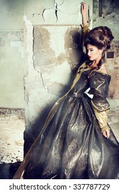Art Fashion. Beautiful young woman in elegant historical dress and with barocco updo hairstyle posing in the ruins of the castle. Renaissance. Barocco.