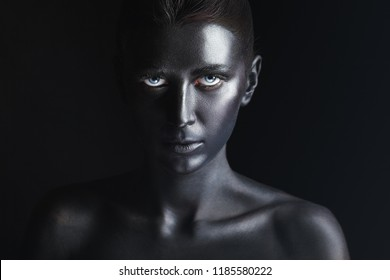 Art fashion makeup. An amazing young woman with black makeup against a dark background