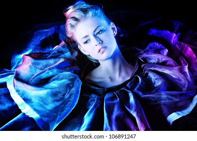 Art fashion photo of a beautiful model. Over black background.