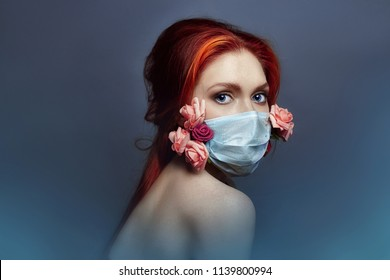 Art fashion redhead woman with medical respirator on her face, rose flowers grow from under mask, clean air lack of oxygen, bad ecology and dirty air. Girl inhales aroma of flowers closing her eyes