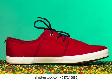 Art fashion street footwear concept. Burgundy sneaker with white sole on shiny beads over bright mint background. Casual, vintage style. Close up. Studio shot