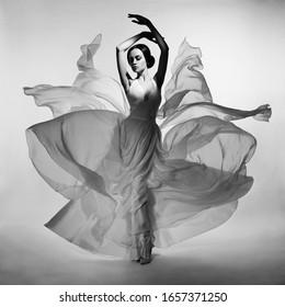Art fashion studio photo of beautiful elegant woman in blowing dress. Flying dress. Freedom concept. Fashion style of flowing dress