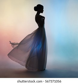 Art fashion studio photo of beautiful elegant woman in blowing dress. Drawing of shadows and colors. Light and color effects. Flying dress. Fashion style of flowing dress