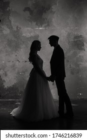 Art fashion studio photo of wedding couple silhouette groom and bride on colors background.