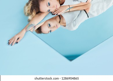 Art fashion studio portrait of elegant blonde woman and her reflection in the mirror on blue or aqua background. Reflection of our mind and soul concept.