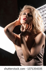 Art and fashion style photo of a beautiful girl with disheveled wet hair, naked shoulders, red lips, touches her face and neck in front of studio light. Commercial and advertising design. Copy space.