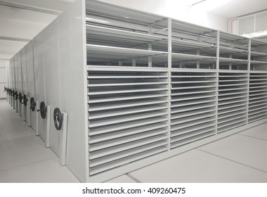 Art history museum depository warehouse archive empty grey shelves and storage space.