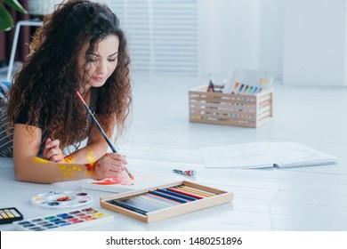 Art hobby leisure. Woman creating abstract painting. Colored pencils, palette on white wooden floor.