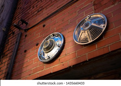 Art hubcaps on red brick wall
