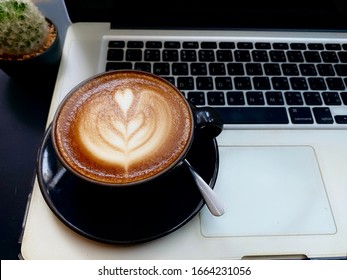 Art latte coffee pass the invention of a milk foam as flower in black mug or cup of coffee and coaster placed on laptop. Showing a break, refresh from negotiation while working in a cafe, shop or home