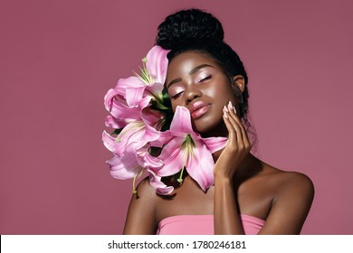 Art make up. Fashion beauty portrait of young African American model touching face with posing with lily flowers against pink background.