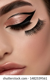 art of make-up artist with false eyelashes and black eyeliner, perfect evening mua with golden colors and sexy lips