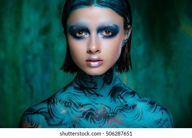 Art make-up in bright colors. Beautiful brunette girl in short hair posing in the studio on a turquoise background. Radiant skin. Space for text. Advertising Space