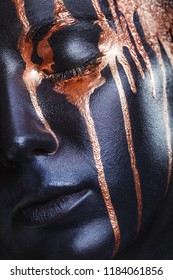 Art makeup. Close-up of a girl with black makeup and leaking gold paint
