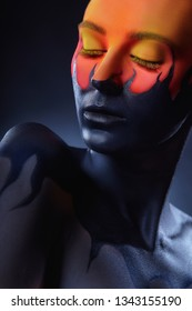 Art make-up. Woman with black-orange makeup and black tongues of flame