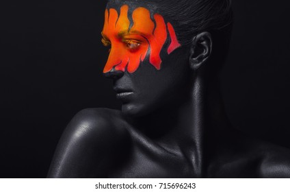 Art make-up. Woman with black-orange makeup and black tongues of flame against a black background. Studio shot