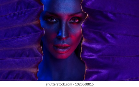 Art neon Portrait of Beautiful Young Woman with make-up. Woman's face surrounded by Ultra Violet colorful frame, a tropical background. Sexy girl and colorful leaves. Nightlife concept. Space for text