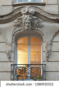 Art nouveau detailing with male head, flowers and balcony around a window  on a building by Albert Prugnaud in 1898 in rue dupont-des-loges in Paris's 7th arrondissement
