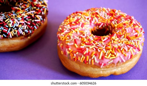 Art Nouveau style concept image, Iced doughnut / donut with sprinkles on a yellow background / multi colored geometric trendy background, food and healthy concept