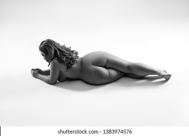 Art nude, perfect naked body, sexy woman on gray background, black and white studio shot, body positive concept