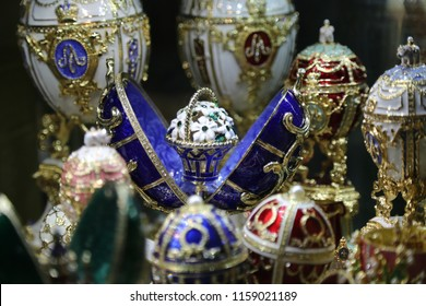 Art objects in Russia, a group of Faberge eggs in various colors including blue, red, pink and white with gold and flower pattern displayed in a museum in St. Peters berg.