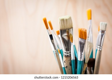 Art paint brushes on light brown wooden background