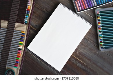 art painting workplace, pencils, brushes, watercolor paints, canva paper and crayon pastel chalks. Flat lay wooden table